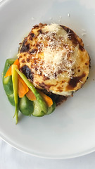 Greek dish Moussaka made of minced meat, cheese and green asparagus on a white plate