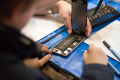 iFixit staff member showing a young boy how to do a teardown of a smart phone