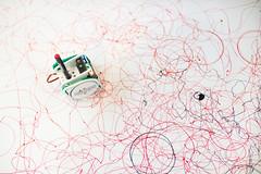 Kleiner Roboter mit Stift kritzelt auf einer weißen Fläche