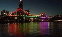 Brisbane. The Story Bridge with coloured lights at dusk from the Brisbane River.