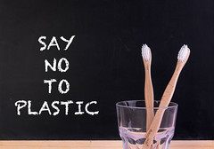 Wooden toothbrushes in a glass with say no to plastic text
