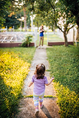 A girl walking down the path towards her mother