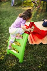 A little girl using a ladder to climb a slide