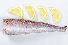 Top view of raw hake fish with lemon slices
