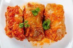 Three stuffed cabbage rolls in tomato sauce on a white plate