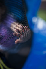 Toddler's hand on a tramboline safety net. Symbol of carefree childhood