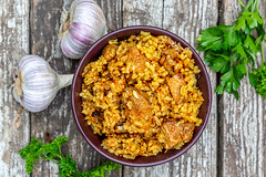 Top view of a bowl of meat pilaf on a wooden gray background with fresh parsley and garlic