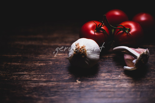 Garlic bulbs with vine tomatoes on wooden vintage background. Cl