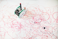 Small robot with pen doodling on a large white surface