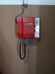Analog card telephone on the hospital wall. Symbol of stagnation