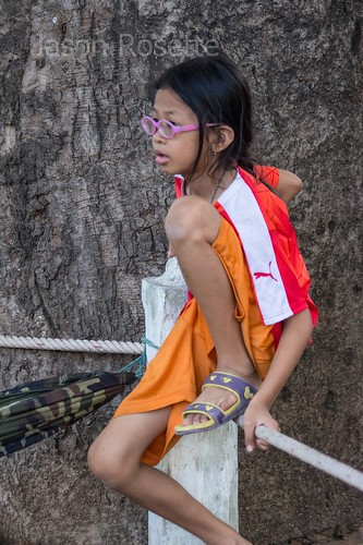 Skinny girl with glasses watches Cambodian boat race event in Asia