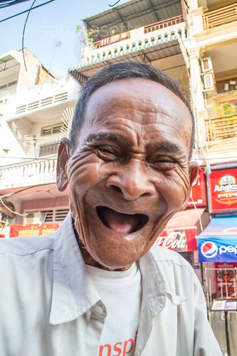 Laughing octogenarian cyclo driver in Cambodia