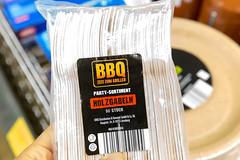 Hand hält Holzgabeln in einer Plastikverpackung, als Partyutensilien für den Grillabend