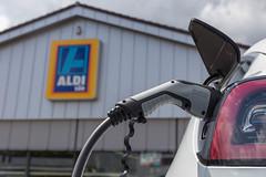 Elektroauto laden: Tesla Model 3 mit einem Typ 2 Ladestecker, tankt Sonnenenergie vor dem Aldi-Süd Supermarkt