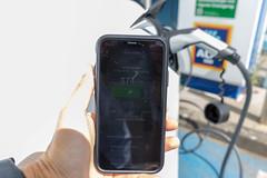 Smartphone-App zeigt den Ladebalken in km an, während  das Tesla E-Auto auf einem Aldiparkplatz mit Sonnenenergie geladen wird