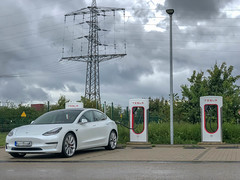 E-Mobilty: White electric car Tesla Model 3 at a Supercharging-Station in Erftstadt, Germany