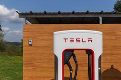 """Ladesäule """"Supercharger"""" von Tesla, zum Schnellladen von Elektrofahrzeugen, vor einer Holzwand"""