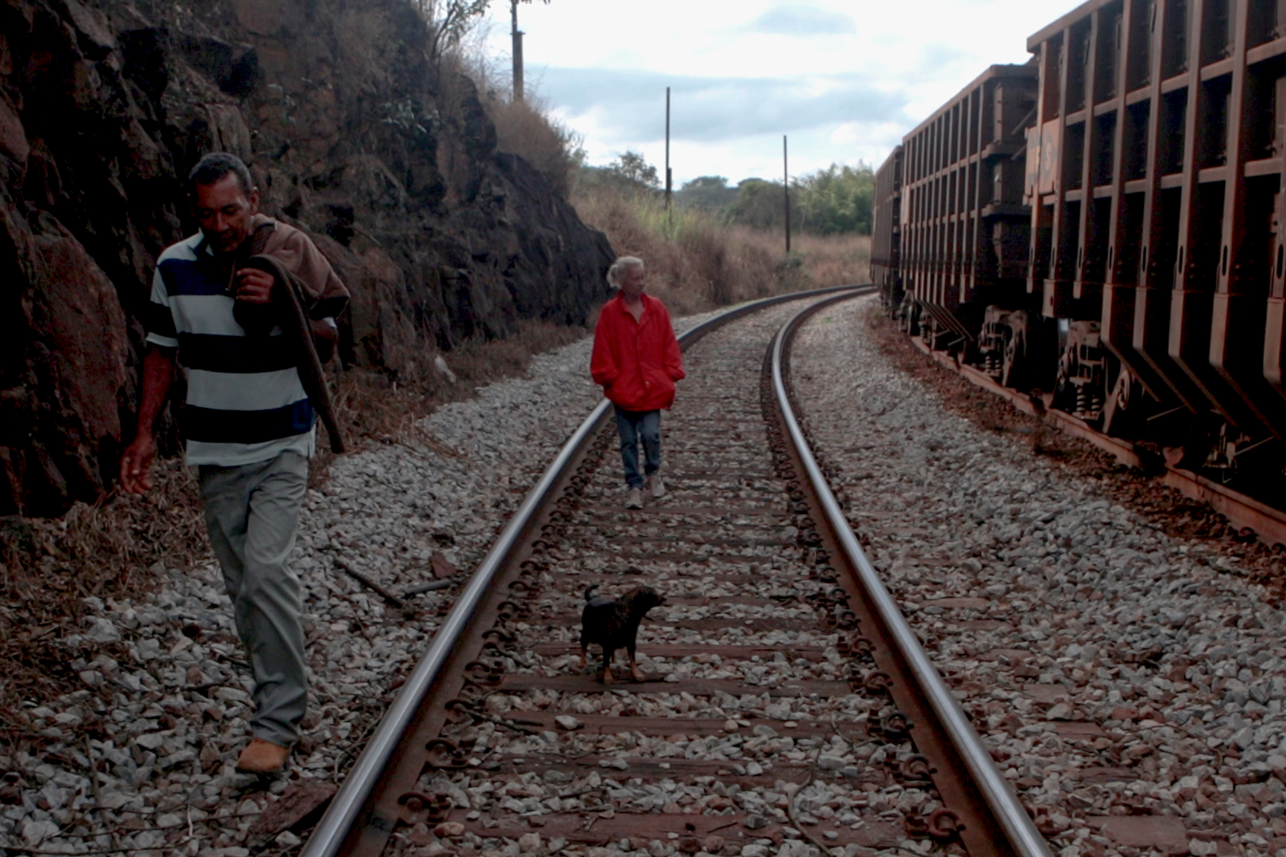 The couple Fátima de Jesus and Oswaldo Zacarias walk alongside Vale's train tracks. The miner's train keeps running late at night and makes it difficult for Pires residents to move around