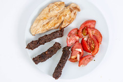 Flat lay above served grilled Chicken Breasts with Kebabs and Tomatoes