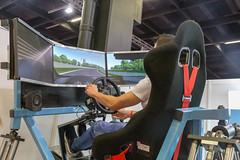 Gamescom visitor tests a GT Chassis racing seat with seatbelt, for car racing video games
