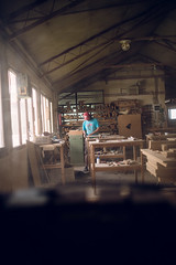 A young man working alone in a furniture workshop