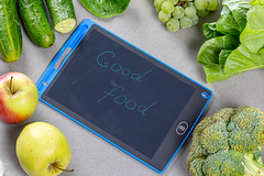 """Fresh ripe green fruits and vegetables surround the inscription """"good food"""" on a gray background. Top view"""
