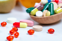 Close-up of medication in capsules and pills in a wooden spoon