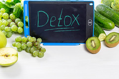 """Ripe green fruits and vegetables on a white background with the inscription """"detox"""""""