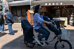 A lady rides by on her bicycle near the Senso-ji temple