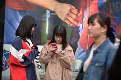 Texting teens just outside the Takeshita fashion street