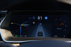 Electric Car Tesla Model S driving in autopilot - instrument panel / cluster shows street camera, navigation system and speed indicator