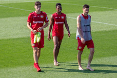 Three soccer players Lucas Alario, Wendell and Kai Havertz leaving the pitch happy and barefoot after their training in Germany