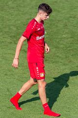 Junger Fußballer Kai Havertz läuft nach dem Fußballtraining Barfuß in roten Socken über das Spielfeld