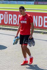 Der Kölner Fußballspieler Ellyes Skhiri läuft nach dem Training mit Fußballschuhen über das Gelände vorm Mannschaftsclubhaus