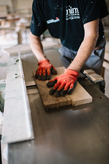 Experienced carpenter processing a piece of wood with a planer