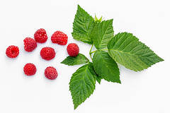 Fresh raspberry berries with leaves on white background