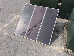 Solar Panels with the reflection of a communications tower