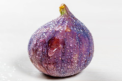 Fresh figs with water drops on white background