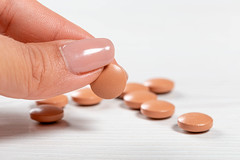 Brown pills on a white wooden background and one in a woman's hand