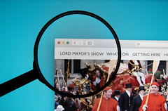 The Lord Mayor's Show website on a computer screen with a magnifying glass