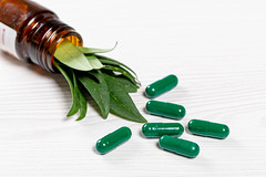 Close-up of green medical capsules with fresh green leaves in a glass bottle