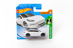 White miniatur Tesla toy car by Hot Wheels (Mattel) of the HW Green Speed Collection,  brand new and boxed, in front of white background