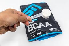 Hand hält einen Messlöffel mit Aminosäure-Pulver Nitro BCAA von ESN über die wiederverschließbare Verpackung