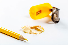 Yellow pencil, sawdust and pencil sharpener on white background