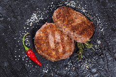 Grilled meat patties with salt and chili pepper. Top view