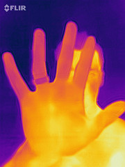Thermal imaging camera takes a picture of a man with his hand outstretched in front of his face