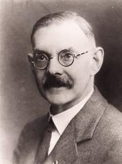Shán Ó Cuív, head and shoulders portrait, facing left, wearing eyeglasses
