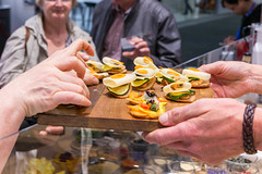Exhibition chef hands over finger food on a wooden board to IFA fair visitors