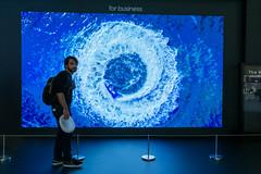 """Mann steht zum Größenvergleich vor dem riesigen Samsung-Bildschirm """"The Wall"""", mit LED Chip und Black Seal-Technologie"""