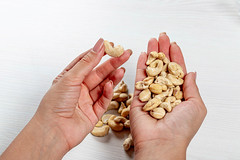 Female hands with cashew nuts. Healthy food concept